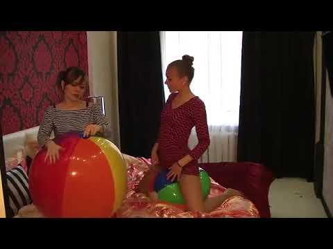 Две сексуальные девушки сдувают пляжные мячики